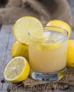 Glas mit Zitronensaft und einer Scheibe Zitrone am Rand